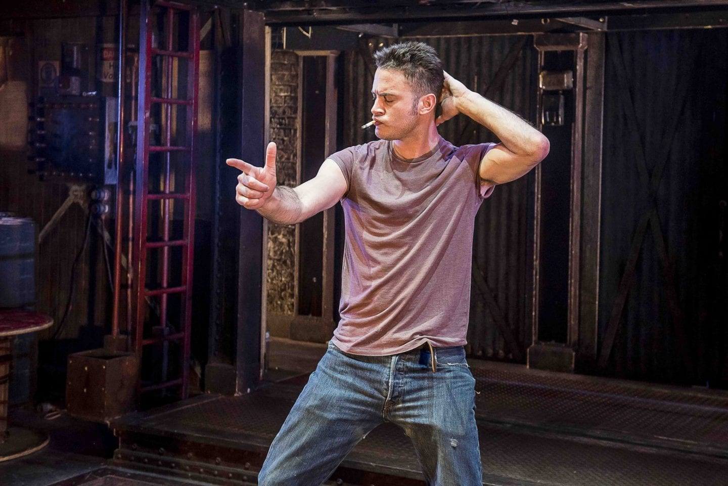 Actor Gary Lucy wearing well worn blue denim jeans and a faded red T-shirt. Disco dancing with a sell confident expression, and cigarette in his mouth. Whilst playing the Full Monty character Gaz.